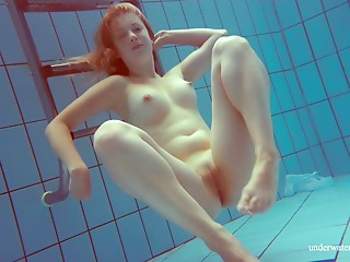 Sexual redhead honey unveils her pink muff whilst diving in the pool