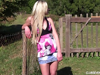 Blond in the backyard sits in the grass and masturbates